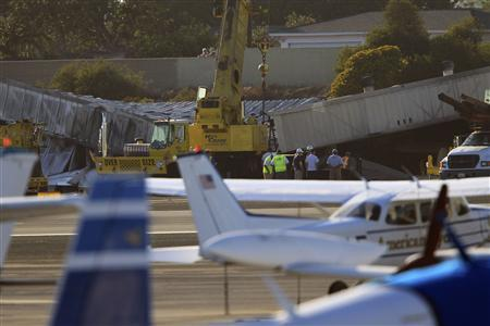 Workers prepare to use cranes to extract a twin-engine Cessna Citation 525A aircraft from inside a collapsed hangar which it slammed into, bursting into flames, after it touched down last night, in Santa Monica, California, September 30, 2013. REUTERS/David McNew