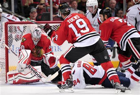 Oct 1, 2013; Chicago, IL, USA; Chicago Blackhawks goalie Corey Crawford (50) makes a save in front of center Jonathan Toews (19) and Washington Capitals center Mikhail Grabovski (84) during the third period at the United Center. The Blackhawks beat the Capitals 6-4. Mandatory Credit: Rob Grabowski-USA TODAY Sports