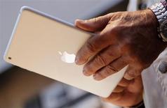 Покупатель держит планшет iPad mini в магазине Apple в Пало-Альто, Калифорния, 2 ноября 2012 года. Apple Inc не сможет выпустить в этом месяце новую версию iPad Mini с дисплеем высокого разрешения retina, сообщили люди, работающие в системе поставок компании. REUTERS/Robert Galbraith