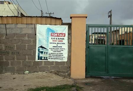 A sign advertising the sale of a house is pasted on a wall in the Victoria Island district in Nigeria's commercial capital Lagos September 10, 2013. REUTERS/Akintunde Akinleye
