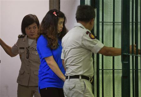 Noppawan Tangudomsuk (C) is detained by criminal court officers at the criminal court in Bangkok October 2, 2013. REUTERS/Athit Perawongmetha