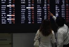 Люди изучают электронное табло с котировками на бирже в Токио 9 сентября 2013 года. Азиатские фондовые рынки, кроме Японии, выросли в среду за счет локальных факторов. REUTERS/Yuya Shino