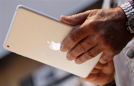 10月2日、米アップルが近く発売する次期「iPad mini(アイパッドミニ)」について、中核部品となる高精細液晶ディスプレーの生産が遅れていることがわかった。写真は昨年11月、米カリフォルニア州で現行の同製品を手にする男性(2013年 ロイター/Robert Galbraith)