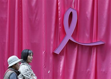 Visitors walk past a sculpture of a pink ribbon installed to promote the ''Pink Ribbon'' breast cancer awareness campaign at Cheonggye Stream in central Seoul October 5, 2011. REUTERS/Jo Yong-Hak