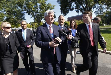 Jamie Dimon (C), Chairman and CEO of JPMorgan Chase, is questioned by journalists as he and other CEOs arrive at the White House in Washington October 2, 2013, for a meeting of the Financial Services Forum with U.S. President Barack Obama. REUTERS/Jason Reed