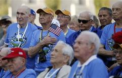A veteran puts his hand on his heart as he and fellow veterans of the Heartland Honor Flight gather at the World War Two Memorial in Washington October 2, 2013. REUTERS/Kevin Lamarque