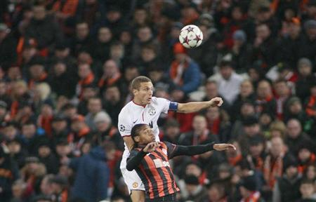 Shakhtar Donetsk's Luiz Adriano fights for the ball with Manchester United's Nemanja Vidic (top) during their Champions League soccer match at the Donbass Arena in Donetsk October 2, 2013. REUTERS/Gleb Garanich