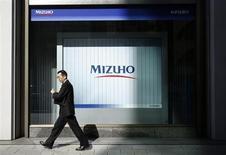 A man walks past a branch of Mizuho bank belonging to Mizuho Financial Group in Tokyo February 25, 2013. REUTERS/Yuya Shino