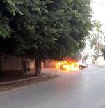 Горящая машина у подвергнувшегося атаке посольства России в Триполи 2 октября 2013 года. Посольство России в столице Ливии Триполи подверглось обстрелу в среду, когда группа неизвестных попыталась прорваться в комплекс дипломатических зданий, сообщило министерство иностранных дел РФ. REUTERS/Stringer