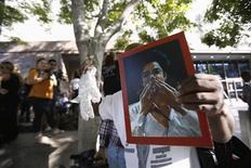 """Поклонник Майкла Джексона держит фотографию покойного певца и белую перчатку у здания суда в Лос-Анджелесе после объявления вердикта по иску против AEG Live 2 октября 2013 года. Суд присяжных Лос-Анджелеса признал концертного промоутера AEG Live непричастным к смерти """"короля поп-музыки"""" Майкла Джексона. REUTERS/Mario Anzuoni"""