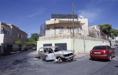A damaged car is seen in front of the Russian embassy, a day after it came under attack in Tripoli October 3, 2013. REUTERS/Ismail Zitouny