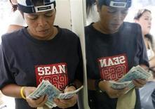 Женщина пересчитывает филиппинские песо в обменном пункте Манилы 15 октября 2007 года. Переводы денег трудовых мигрантов на родину вырастут в этом году на 6,3 процента до $414 миллиардов и помогут развивающимся странам компенсировать отток капитала, ожидает Всемирный банк. REUTERS/Cheryl Ravelo
