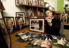 Продавец Владимир Тышко вставляет в раму фотографии Владимира Путина и Дмитрия Медведева для их последующей продажи в магазине в Москве 28 февраля 2008 года. Российское правительство в поиске стимулов для замедляющейся экономики вновь обратилось к $90-миллиардному пенсионному стабфонду, половину которого Владимир Путин разрешил вложить в инфраструктуру, и думает пустить часть Фонда национального благосостояния на кредиты малому бизнесу через госкорпорацию ВЭБ и банки. REUTERS/Sergei Karpukhin