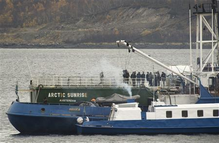 Captain Peter Willcox (5th R), an American, captained the Arctic Sunrise during a protest near the Prirazlomnaya oil platform, and federal Investigative Committee employees and Interior Ministry members are seen onboard the Arctic Sunrise vessel anchored outside the Arctic port city of Murmansk, in this October 2, 2013 handout provided by Greenpeace. REUTERS/Dmitri Sharomov/Greenpeace/Handout via Reuters