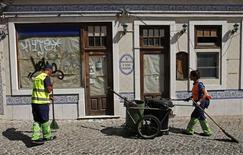Imagen de archivo de unos barrenderos frente a un restaurante cerrado en Alges, Portugal, ago 26 2013. Los prestamistas internacionales de Portugal aprobaron el desempeño económico del país en su última examinación al desarrollo del programa de rescate, que ha empezado a ofrecer resultados positivos, dijo el viceprimer ministro Paulo Portas. REUTERS/Jose Manuel Ribeiro