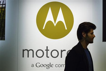 A man walks past a Motorola logo at a launch event for Motorola's new Moto X phone in New York, August 1, 2013. REUTERS/Lucas Jackson