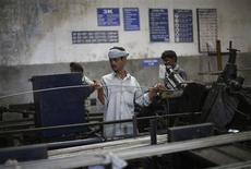 An employee holds a steel rod as he works on the production line inside Hallmark steel factory in Bhiwadi in the desert Indian state of Rajasthan September 30, 2013. REUTERS/Adnan Abidi