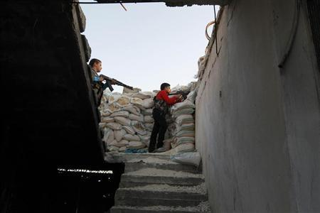 Abboud (L), 12, and his brother Deeb, 14, stand with their weapons behind sandbags in Aleppo's Sheikh Saeed neighbourhood, September 28, 2013. REUTERS/Muzaffar Salman