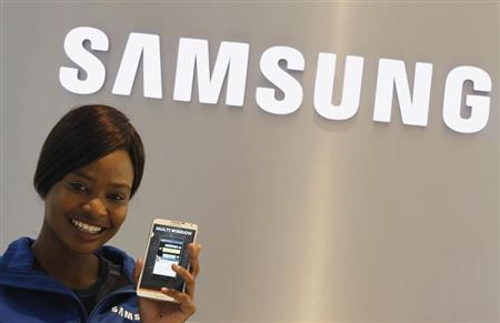 A Samsung employee holds a mobile phone at a Samsung display store in Johannesburg, October 3, 2013. REUTERS/Siphiwe Sibeko