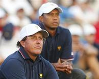 U.S. teammates Tiger Woods (R) and Phil Mickelson watch play after finishing their matches during the opening Four-ball matches for the 2013 Presidents Cup golf tournament at Muirfield Village Golf Club in Dublin, Ohio October 3, 2013. REUTERS/Chris Keane