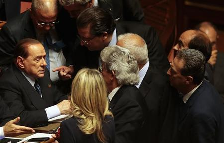 Italian center-right leader Silvio Berlusconi (L) talks with senators at the Senate after Italy's Prime Minister Enrico Letta's asking for a possible call for a confidence vote immediately in Rome, October 2, 2013. REUTERS/Tony Gentile
