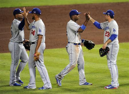 Oct 3, 2013; Atlanta, GA, USA; Los Angeles Dodgers first baseman Adrian Gonzalez (23) and right fielder Yasiel Puig (center) celebrate after defeating the Atlanta Braves in game one of the National League divisional series playoff baseball game at Turner Field. The Dodgers won 6-1. Mandatory Credit: Dale Zanine-USA TODAY Sports