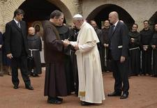 Pope Francis signs a book as he arrives at the San Damian monastery during his pastoral visit in Assisi October 4, 2013. REUTERS/Gian Matteo Crocchioni/Pool