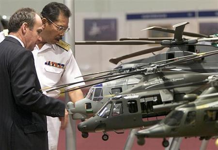 Visitors look at AgustaWestland model helicopters during Heli-Asia exhibition in Kuala Lumpur October 22, 2002. REUTERS/Zainal/Files