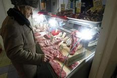 Мужчина в мясной лавке в Москве 8 февраля 2013 года. Рост потребительских цен в России в сентябре 2013 года замедлился 6,1 процента в годовом выражении с 6,5 процента в августе и 6,6 процента в сентябре 2012 года, сообщил Росстат. REUTERS/Mikhail Voskresensky