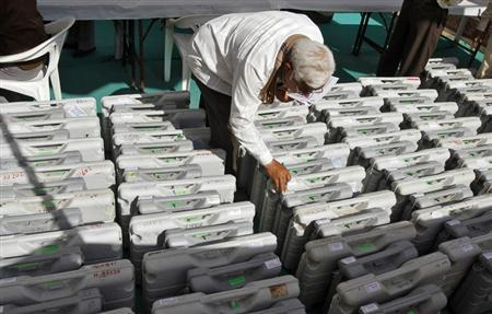 A polling official checks a tag on an electronic voting machine at a distribution centre ahead of state assembly polls in Sanand, Gujarat December 12, 2012. REUTERS/Amit Dave/Files