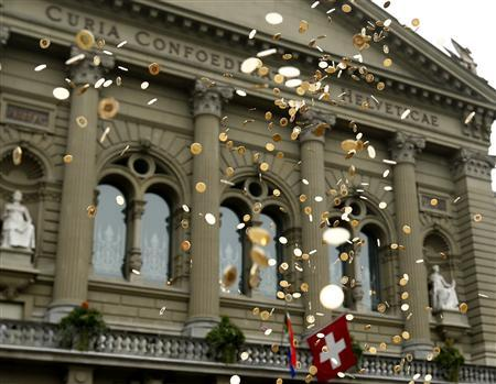 Five cent coins are pictured in the air in front of the Federal Palace during an event organised by the Committee for the initiative ''CHF 2,500 monthly for everyone'' (Grundeinkommen) in Bern October 4, 2013. REUTERS/Denis Balibouse