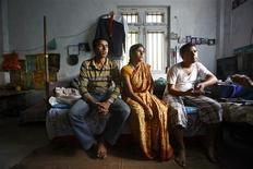 Raju Prasad Lamichhane (L) , mother Mun Maya and brother Dilli speak during an interview at their half-finished house in Telkot village, near Kathmandu October 1, 2013. REUTERS/Navesh Chitrakar