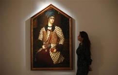 "A Sotheby's employee poses with ""A Portrait of Rustam Khan Zand"" by Muhammad Sadiq from the early 1779 at Sotheby's in London October 4, 2013. REUTERS/Suzanne Plunkett"