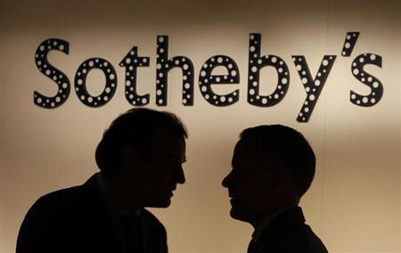 Two men chat in front of a polka dot covered Sotheby's signage, part of an installation by Japanese artist Yayoi Kusama, at Sotheby's newly opened gallery in Hong Kong May 18, 2012. REUTERS/Bobby Yip