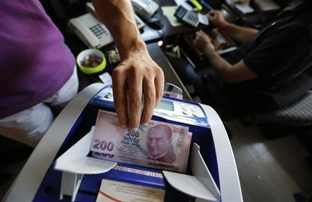 A money changer uses a machine to count Turkish liras in the border city of Hatay September 17, 2013. REUTERS/Umit Bektas