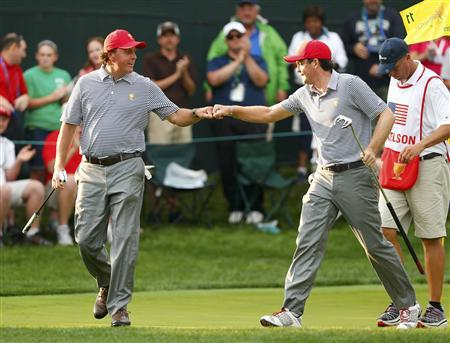 U.S. teammates Phil Mickelson (L) and Keegan Bradley bump fists after winning the 11th hole against International teammates Jason Day of Australia and Graham DeLaet of Canada during the Foursome matches for the 2013 Presidents Cup golf tournament at Muirfield Village Golf Club in Dublin, Ohio October 4, 2013. REUTERS/Chris Keane