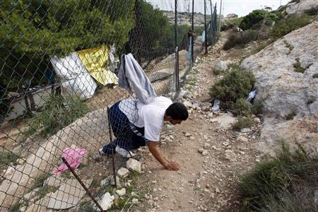 A migrant leaves the immigration centre through a fence on the southern Italian island of Lampedusa October 5, 2013. REUTERS/Antonio Parrinello