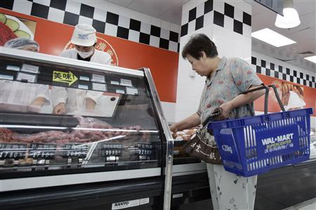 A shopper looks at the meat section of Wal-Mart Supercenter branch in Beijing August 9, 2006. REUTERS/Claro Cortes IV