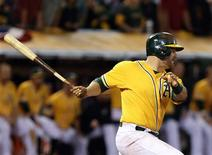 Oct 5, 2013; Oakland, CA, USA; Oakland Athletics catcher Stephen Vogt (21) hits an RBI single for the walk off win against the Detroit Tigers in game two of the American League divisional series playoff baseball game at O.co Coliseum. The Oakland Athletics defeated the Detroit Tigers 1-0 with a walk off win. Mandatory Credit: Kelley L Cox-USA TODAY Sports