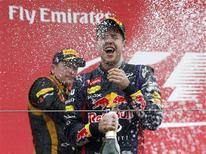 Second placed Lotus Formula One driver Kimi Raikkonen of Finland (L) sprays champagne at winner Red Bull Formula One driver Sebastian Vettel of Germany on the podium after the Korean F1 Grand Prix at the Korea International Circuit in Yeongam, October 6, 2013. REUTERS/Kim Hong-Ji