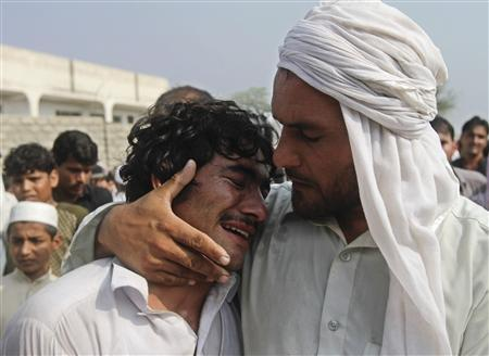 An Afghan man cries over the dead body of his brother, who according to the provincial government, was killed in a NATO air strike, on the outskirts of Jalalabad province, October 5, 2013. REUTERS/ Parwiz