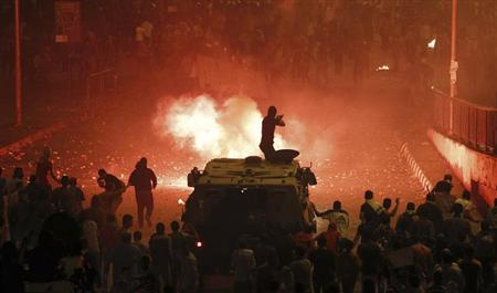 A riot police officer, on a armoured personnel carrier surrounded by anti-Mursi protesters (foreground), fires rubber bullets at members of the Muslim Brotherhood and supporters of ousted Egyptian President Mohamed Mursi along a road at Ramsis square, which leads to Tahrir Square, during clashes at a celebration marking Egypt's 1973 war with Israel, in Cairo October 6, 2013. REUTERS/Amr Abdallah Dalsh