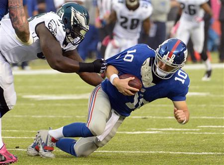 Oct 6, 2013; East Rutherford, NJ, USA; New York Giants quarterback Eli Manning (10) is sacked by Philadelphia Eagles defensive tackle Bennie Logan in the fourth quarter during the game at MetLife Stadium. Mandatory Credit: Robert Deutsch-USA TODAY Sports