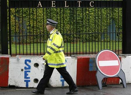 A police officer walks past a security barrier at the Wimbledon tennis championships in London, July 2, 2007. REUTERS/Toby Melville
