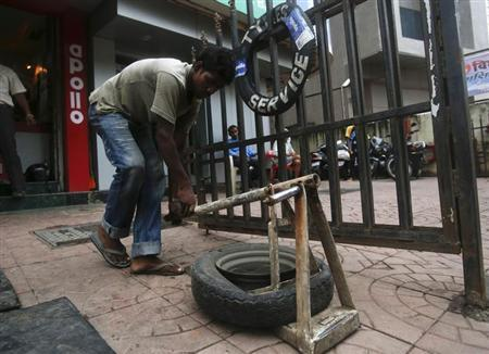 A labourer removes a punctured Apollo tyre outside an Apollo Tyres workshop in Mumbai, June 13, 2013. REUTERS/Vivek Prakash/Files