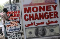 Мужчина просит милостыню у пункта обмена валюты в Дели 21 августа 2013 года. Американская валюта снизилась к иене и швейцарскому франку в понедельник на фоне отсутствия признаков выхода американской политической элиты из тупика в ходе переговоров о федеральном бюджете. REUTERS/Adnan Abidi