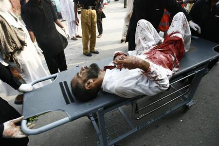 ATTENTION EDITORS - VISUAL COVERAGE OF SCENES OF INJURY OR DEATH - A man injured in a bomb blast is wheeled on a stretcher as he arrives at the Lady Reading Hospital for treatment in Peshawar October 7, 2013. REUTERS/Khuram Parvez