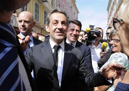 Former French president Nicolas Sarkozy (C) greets well-wishers as he arrives for a lunch with the Mayor of Nice, Christian Estrosi (R) and UMP political party members in Nice September 27, 2013. REUTERS/Olivier Anrigo