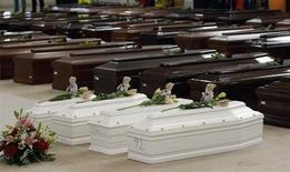 Гробы утонувших мигрантов в ангаре аэропорта Лампедузы 5 октября 2013 года. Итальянские спасатели нашли тела 194 африканцев, в минувший четверг пытавшихся на небольшом судне достигнуть итальянского побережья, сообщили власти. REUTERS/Antonio Parrinello
