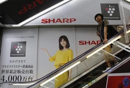 A man rides an escalator past Japanese display maker Sharp Corp's advertisements at an electronics retail store in Tokyo May 14, 2013. REUTERS/Toru Hanai